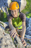 Smiling woman, rock climber in yellow helmet. Stock Photo
