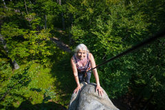 Smiling woman rockclimber is reaching top of the rock Stock Image