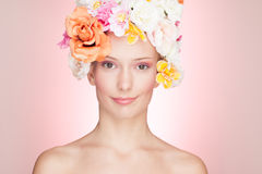 Smiling Woman with Roses Hat. Portrait of a smiling woman in a hat made of roses, on pink background Stock Photo