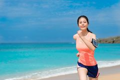 Smiling woman runner carrying technology device. Smiling pretty woman runner carrying technology device and wearing sportswear going to beach running workout Royalty Free Stock Image