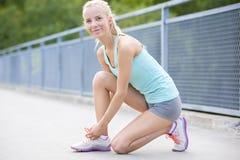 Smiling woman runner tying shoelaces on bridge Stock Photography