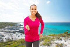 Smiling woman running on beach Stock Photos