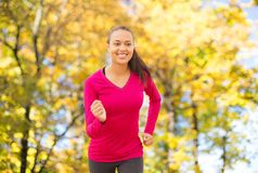 Smiling woman running outdoors at autumn Royalty Free Stock Photo