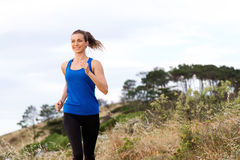 Smiling woman running outside in sportswear Stock Photos