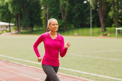 Smiling woman running on track outdoors. Fitness, sport, training and lifestyle concept - smiling african american woman running on track outdoors Royalty Free Stock Photography