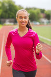 Smiling woman running on track outdoors. Fitness, sport, training and lifestyle concept - smiling african american woman running on track outdoors Royalty Free Stock Photo