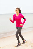 Smiling woman running on track outdoors Stock Image