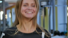 Smiling woman running on treadmill in the gym stock video footage