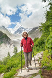 Smiling woman runs on mountain trail Royalty Free Stock Image