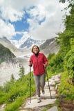 Smiling woman runs on mountain trail Royalty Free Stock Image