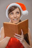 Smiling woman in Santa Claus clothes with book Royalty Free Stock Image