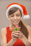 Smiling woman in Santa Claus clothes with flower Royalty Free Stock Images