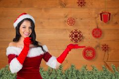 Smiling woman in santa costume pretending to catch snowflake Stock Photo