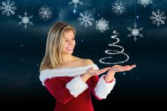 Smiling woman in santa costume pretending to hold a imaginary christmas tree. Against digitally generated background Royalty Free Stock Image