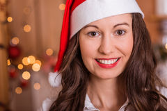 Smiling Woman in Santa hat. Young Girl preparing for Christmas and holding hot tea / coffee Royalty Free Stock Photos
