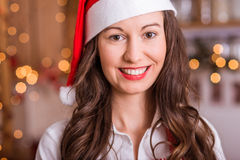 Smiling Woman in Santa hat. Young Girl preparing for Christmas and holding hot tea / coffee Stock Photo