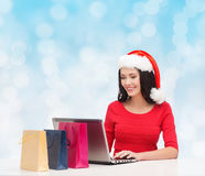 Smiling woman in santa hat with bags and laptop Stock Photo
