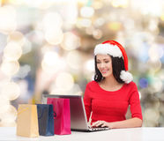 Smiling woman in santa hat with bags and laptop Royalty Free Stock Photo
