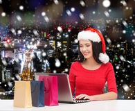 Smiling woman in santa hat with bags and laptop Royalty Free Stock Image