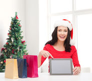 Smiling woman in santa hat with bags and tablet pc. Holidays, technology, advertising and people concept - smiling woman in santa helper hat with shopping bags Stock Photo