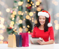 Smiling woman in santa hat with bags and tablet pc Stock Photography