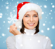 Smiling woman in santa hat with big snowflake Royalty Free Stock Photo