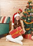 Smiling woman in santa hat with gift box sitting under Christmas tree. Merry Christmas and Happy New Year concept Royalty Free Stock Photo