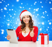Smiling woman in santa hat with gift and tablet pc Royalty Free Stock Photo
