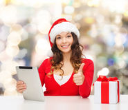 Smiling woman in santa hat with gift and tablet pc Royalty Free Stock Photos