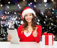 Smiling woman in santa hat with gift and tablet pc Royalty Free Stock Images