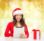 Smiling woman in santa hat with gift and tablet pc Stock Photography