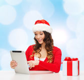 Smiling woman in santa hat with gift and tablet pc Stock Photos