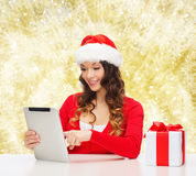 Smiling woman in santa hat with gift and tablet pc Royalty Free Stock Image