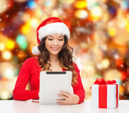 Smiling woman in santa hat with gift and tablet pc Stock Photo