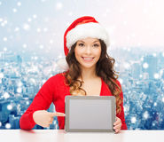 Smiling woman in santa hat with gift and tablet pc Stock Image