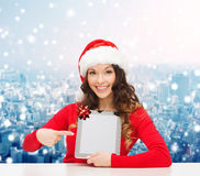 Smiling woman in santa hat with gift and tablet pc Royalty Free Stock Photography