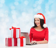Smiling woman in santa hat with gifts and laptop Royalty Free Stock Photography
