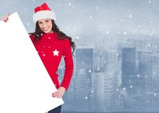 Smiling woman in santa hat holding a blank placard. Against digitally generated city background Royalty Free Stock Photography