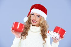 Smiling woman in Santa hat holding Christmas gifts Stock Photos