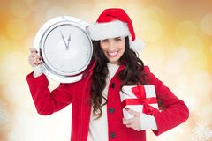 Smiling woman in santa hat holding a clock and christmas gift Royalty Free Stock Images