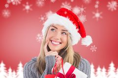 Smiling woman in santa hat holding a gift bag Royalty Free Stock Photo