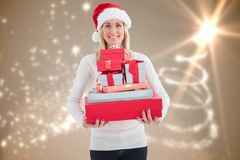 Smiling woman in santa hat holding stack of christmas gifts Royalty Free Stock Photos