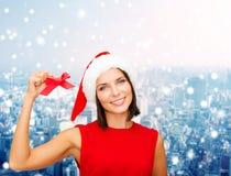Smiling woman in santa hat with jingle bells Стоковая Фотография