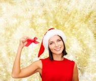 Smiling woman in santa hat with jingle bells Стоковые Фото