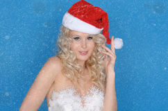 Smiling woman in Santa hat and snow Royalty Free Stock Image