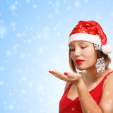 Smiling woman in santa hat on snowflakes background Stock Image