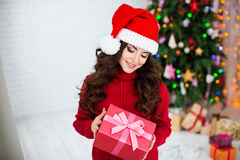 Smiling woman in in Santa hats holding red gift box over christmas tree lights background. Stock Image