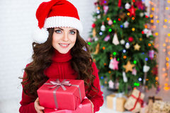 Smiling woman in in Santa hats holding red gift box over christmas tree lights background. Royalty Free Stock Photo
