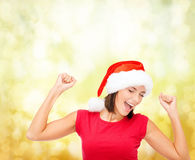 Smiling woman in santa helper hat. Christmas, winter, holidays, happiness and people concept - smiling woman in santa helper hat and blank red shirt over yellow Stock Photos