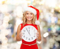 Smiling woman in santa helper hat with clock Royalty Free Stock Photo